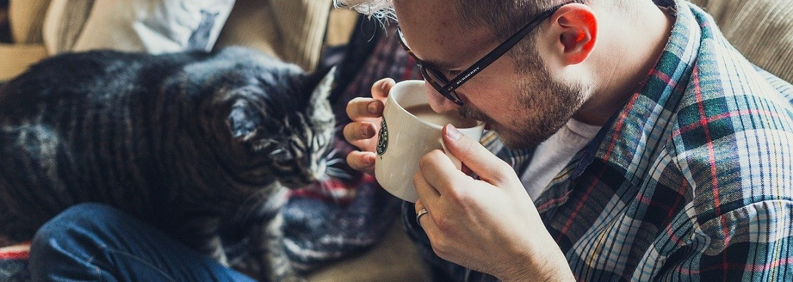 Man drinking a coffee with a cat next to him